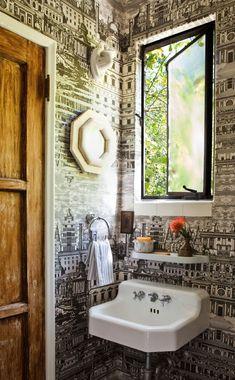 wood door, black and white wallpaper, pedestal sink, shelf above sink, black window, no mirror above sink, bath, bathroom