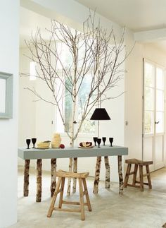 Une table avec plateau en contreplaqué et pieds en tronc de bouleau, avec arbre entier au milieu