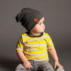 """Knit 90% cotton 10% spandex blend Charcoal Ribbed beanie. Fabric is lightweight and super soft, comfortable to wear any season. Premium leather tag.  Each beanie is handmade and serged for durability. This slouchy beanie is a great addition to your child's wardrobe. Made in the USA.      Size   /   Circumference /   Fits Like  _____________________________________  3-6M/    14.5""""    /     15.5"""" - 17.5""""  6-12M/    15.5""""    /     16.5""""-18.5""""  12-24M/    16.5""""    /     17.5""""-19.5""""…"""