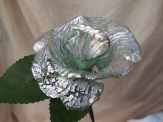 This was made by heating a CD then stretching and forming it as it cools. #recycle art #recycled cd's #cd flowers #cds recycled