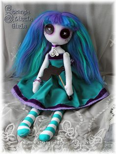 A custom button eyed doll in turquoise and purple, featuring a 'moustache on a stick'