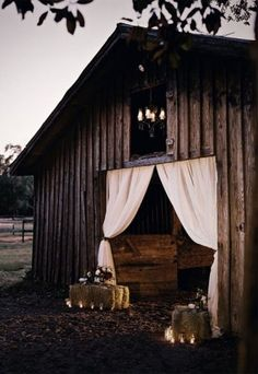 barn wedding- Hay bail with lights around it and flowers on top.  Door swag by Hillenbrand