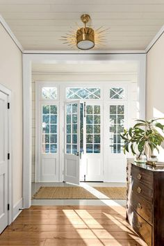 The transom and sidelights surround the front door, flooding the interior with light.