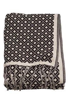 Pléd z žakárové tkaniny: Žakárově tkaný pléd z bavlněné směsi. Na kratší straně lemovaný třásněmi.