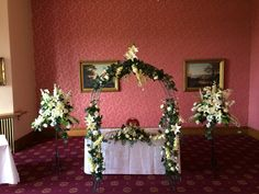 Wedding ceremony in The Douglas Suite, Haigh Hall dressed with bridal arch, two pedestal displays and registrars table design.  Lovely natural greenery and ivorys.  www.am-flowers.co.uk