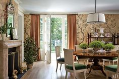 Jansen chairs from Florian Papp encircle a Theodore Alexander dining table from ABC Carpet & Home; the custom-painted wallpaper is from John Rosselli Antiques, and the curtains are made of a Lee Jofa linen with a Samuel & Sons trim.