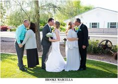 Bride and groom kissing with their parents at Shenandoah Mill wedding in Gilbert, Arizona.