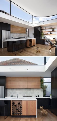 In this modern kitchen, the black and wood cabinets are paired with white countertops and a light grey fish scale patterned tile. A built-in wine rack is included in the design of the kitchen island, and at the end of the upper wood cabinets, curved corner shelves tie in with the shelves above the desk.