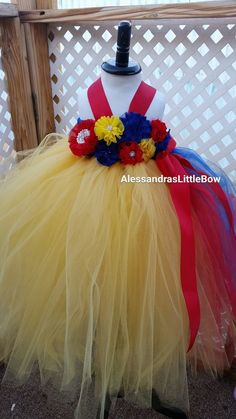 Snow white inspired tutu dress. Bodice if full of beautiful handmade flowers, and rhinestones in yellow, royal blue and red. Made with 100's of yards of tulle for extra fluffiness and better coverage.