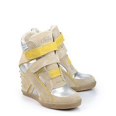 Sneaker von Buffalo in silber-farbener Metallicoptik mit Keilabsatz, dekorativen Kegelnieten, Klettverschlüssen aus Veloursleder und einer gepolsterten Innensohle.