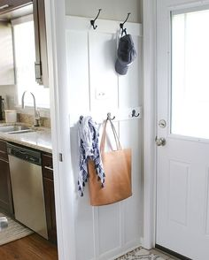 "Extra hooks & board and batten in this tiny space right off the kitchen added a ""secret"" drop zone to a small house. (Read: No more bags + clutter in the kitchen ). Tackle this easy $40 project from DIY Playbook in a weekend!"