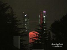 Salida de la luna llena entre árboles y las 4 torres de la Castellana de Madrid