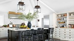 """The kitchen is where we hang out and entertain,"" says Monica Bhargava of her Sonoma house. ""I wanted it to feel soulful, and the Bolton lanterns take me back to the bazaar."" She hung two at either end of the long room to unify the space. Captain barstools by Pottery Barn are pulled up to the large island. """