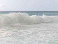 Frothy white sea waves washing up onto the shore.