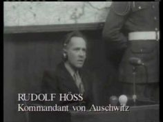Rudolf Franz Ferdinand Hoess, former commandant of the Auschwitz concentration camp, testifies on direct examination before the International Military Tribunal at Nuremberg, April 15, 1946. United States judges Francis Biddle and John J. Parker (drinking water) listen. Questioning is Dr. Kurt Kauffman, attorney for defendant Ernst Kaltenbrunner. Listening at the U.S. prosecution table are attorneys John Harlan Amen, Thomas J. Dodd, Smith Brookhardt, Whitney R. Harris and others.