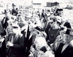 At the reopening of South Fork Bridge in Gold Bridge in the 1940s a man is seen wearing sunglasses and a modern printed t shirt, dressed differently to the surrounding crowd