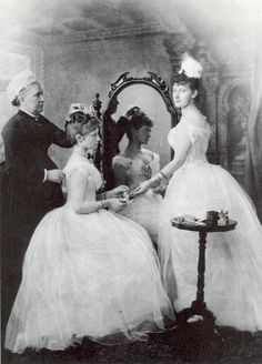 """Alix of Hesse prepares for her first ball in 1889. Arranging her hair is her English nurse, Mrs. Orchard, while her sister Yelizaveta Feodorovna (""""Ella"""") supervises. """""""