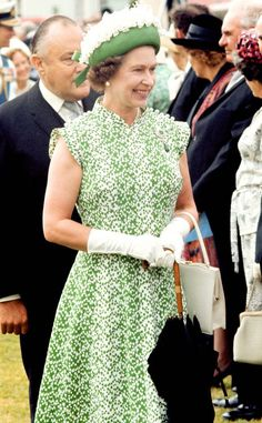 1977 from Queen Elizabeth II's Royal Style Through the Years  Her Royal Highness was all smiles during an outdoor event in a printed green dress and floral-adorned topper.