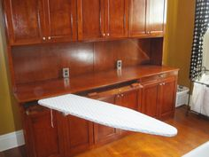 Fold up ironing boards are unsightly and too short. This full size board is sturdy, slides into this narrow compartment, and swings a full 180 degrees! Built in laundry room cabinet