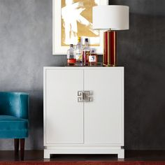 A high-gloss finish combines with Asian-inspired lines in this sleek, contemporary bar cabinet. Designed to house liquor as well as glassware, the cabinet features two shelves for bottles, built-in stemware racks and a drawer for openers and other… White Bar Cabinet, Travertine Coffee Table, Console Table Styling, Contemporary Bar, Ceramic Table Lamps, Cabinet Styles, Glass Table, Bars For Home, Colored Glass