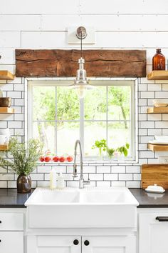 Farmhouse Sink  Every farmhouse needs a farmhouse sink. This Oklahoma home's kitchen features custom cabinetry topped with quartz countertops and complementary subway tile with black grout.
