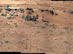 "This patch of windblown sand and dust downhill from a cluster of dark rocks is the ""Rocknest"" site, which has been selected as the likely location for first use of the scoop on the arm of NASA's Mars rover Curiosity. This view is a mosaic of images taken by the telephoto right-eye camera of the Mast Camera (Mastcam) during the 52nd Martian day, or sol, of the mission (Sept. 28, 2012), four sols before the rover arrived at Rocknest. CREDIT: NASA/JPL-Caltech/MSSS"
