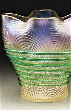 "Loetz vase is a spiraloptisch variant with heavy green threading spiraling up the side of the vase with spirals and lines decorating the clear, slightly iridescent body of the vase. The lip is finished with four pinched sides. Unsigned. Dimensions:5"" x 5""."