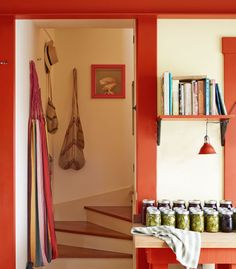 A hammock, a hat, and market bags—all souvenirs from Panama—line the curved stairwell. Freshly preserved cucumbers and beets wait to be stored away. The door frame is painted Fireball Orange by Benjamin Moore. Bright idea: To keep his go-to cookbooks within easy reach, Tarr built a simple bracketed shelf.