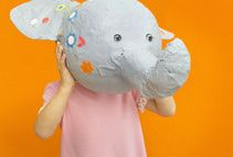 child holding paper mache mask - Mieke Dalle/Photographer's Choice RF/Getty Images