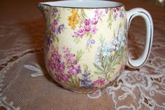 """Beautiful original/vintage chintz cream pitcher/jug dating to the 1920's to 40's. The charming """"Heather"""" pattern was made in England by Lord Nelson Ware and features delicate lavender, white, pink and yellow heather sprays set against a yellow dotted background."""