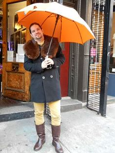 A masculine Swiss man who deals fresh water pearls, rocks a fur lapel and knee high leather boots with our Copper Orange Davek Elite Umbrella.