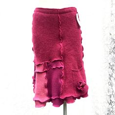 Sweater Skirt, Upcycled Wool Skirt, Patchwork in shades of Fuschia Pink, Handcrafted from a Recycled Wool Sweater, Flower Accent an a pocket near hem, Women Small, (pictures #4 and #5 show the truer color)  Waist 27 up to 34 (with a one inch elastic band) Hips 32 Length 20-23 asymmetrical design  This would please anyone heading off to the office or school campus; an Irish Ceili dance; twirling on the ice skating rink or standing on the street corner waiting for a bus! Pair it with boots…