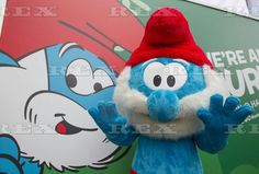 """We're All Smurfs' exhibition, Hong Kong - 12 Jul 2016  An entertainer dressed in a Smurf costume waves during the """"We're All Smurfs"""" art exhibition  12 Jul 2016"""