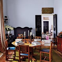 Exotic Dining Room by May Daouk Decoration and Design / A dining room in Beirut features an English Arts and Crafts table and chairs from Ann-Morris Antiques; the calligraphic panel above the door is Syrian, and the carpet is 19th-century Persian. Photography: Simon Watson