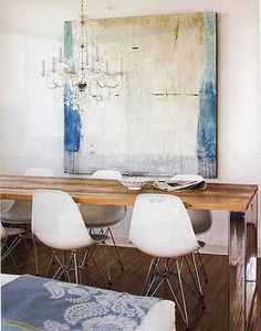A salvaged wood dining table with chrome legs is surrounded by Eames molded plastic chairs, with a crystal chandelier hanging above.