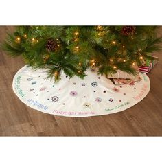 """Wish everyone who enters your home a happy holiday. This hand-embroidered cotton tree skirt from India features holiday greetings in 10 languages (wow!) and tiny hand-embroidered starbursts and accents with shisha mirror centers. Bright colored thread helps each detail pop. Center opening 4 3/4""""dia. Dimensions: 45""""dia. Christmas Decorations, Christmas Tree, Holiday Gifts, Holiday Decor, Green Gifts, Gift Certificates, Gift Baskets, Tree Skirts, Languages"""