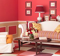 A picture-frame motif repeats in the panel insets on the walls and carpet squares on the floor in this basement living room. The geometry is emphasized with a bold color scheme. The faux wall panels are made from picture-frame molding. Painting the walls a warm red above the chair rail and khaki below gives the area a feeling of intimacy. Applying the same red to the panels creates lively pattern in the wainscoting, and crisp white molding makes the color combination pop