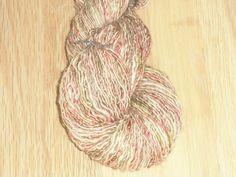 Håndspundet og håndfarvet rødt, grønt og naturfarvet et-trådet supewash merino silke.