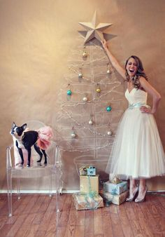 Why is she in a wedding dress. Why is the dog in a tutu. Why is their wall made out of butcher paper. Why is there a drawn-on tree. Why is she decorating the tree with regular decorations instead of drawing them on there. Why is she so freakin excited to be putting the star up on her fake tree. So many questions.