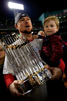 Jon Lester #31 of the Boston Red Sox celebrates with his son Hudson after defeating the St. Louis Cardinals 6-1 in Game Six of the 2013 World Series at Fenway on October 30, 2013.