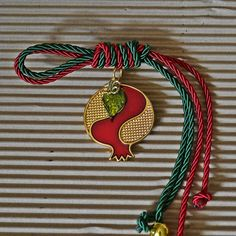 Perforated gold and . Perforated gold and red with enamel, in two-tone cord with metallic elements. Easy Christmas Decorations, Pet Day, Pomegranate, Washer Necklace, Xmas, Bronze, Paracord, Pink, Metallic