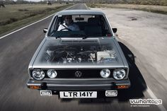 Silver Golf Mk1 GL driving with no bonnet