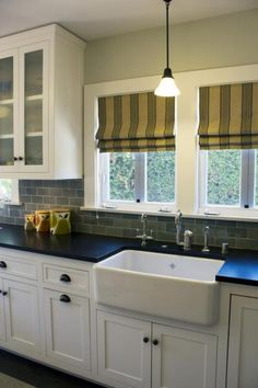 mineral oiled black soapstone with white cabinets and white farmhouse sink. Visit globalgranite.com for your natural stone needs.