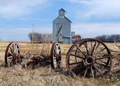 Weathered wooden wagon wheels resting before an abandoned grain elevator on the North side of the tiny town of Flora, ND.