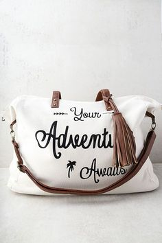 """Excitement is on the horizon with the Adventure Ahead Tan and Cream Weekender! Cream canvas shapes this large weekender bag with, """"Your Adventure Awaits"""" printed in large black letters at front. Tan vegan leather handles and tassel accents. Unzip to reveal a spacious interior with two side pockets and one zipped side pocket. Carry from twin tote handles with a 10"""" drop or clip on the adjustable shoulder strap (measures 45"""" at longest)."""