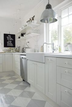 Witte keuken met grijs/wit geschilderde houten vloer.