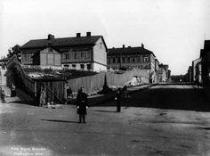 """Poliisi poseeraa kameralle Porthaninkadun ja Hämeenkadun, nykyisen Siltasaarenkadun kulmassa 1908. Hänen takanaan on köyhien lasten työtalo """"Firula"""", jossa työläiskotien lapset työskentelivät ennen kouluunmenoa ja koulun jälkeen. Kuva: Signe Brander."""