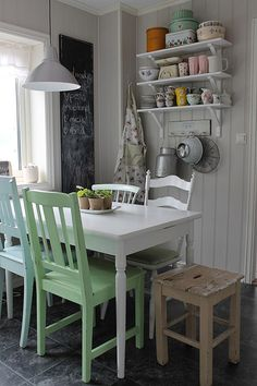 Paint chairs different colors. What a charming little kitchen nook! Cute shelves, too.