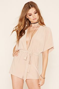 A super-soft knit romper with a plunging V-neckline, an elasticized waist, dropped short sleeves, and a self-tie waist sash.