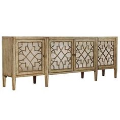 "Wood server with oak veneers and mirrored door fronts.   Product: Server   Construction Material: Hardwood solids, oak veneers and mirrored glass     Color: Natural   Features:   Distressed finish   Adds distinction to any room   Beautiful mirror front    Dimensions: 38"" H x 105"" W x 20"" D"